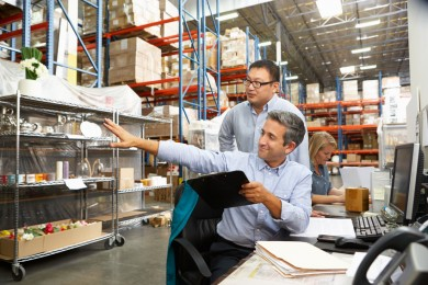 Business Colleagues Working At Desk In Warehouse / © Monkey Business / Fotolia.com.
