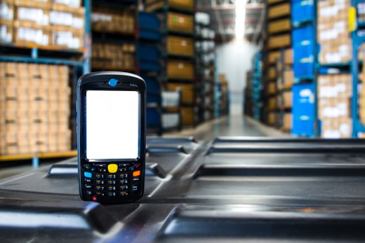Bluetooth barcode scanner in front of modern warehouse / © photoraidz / Fotolia.com.